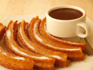 Churros with sugar and a cup of chocolate