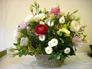 Basket with assorted flowers in white and pink shades