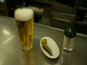 "A ""caña"" (glass of beer) and his ""tapa"" (sardine with olive)"