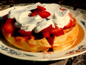 Round waffle with cream and strawberries