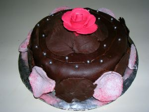 A chocolate cake decorated with chocolate petals and leaves