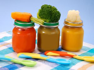 Jars with mashed carrots, broccoli and cauliflower