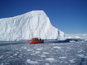 Boat next to an iceberg in Greenland