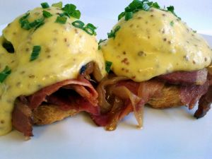Eggs Benedict with bacon and mustard seeds
