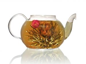 Teapot with tea leaves and flowers