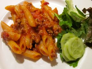 Macaroni with bolognese sauce and cucumber and lettuce salad