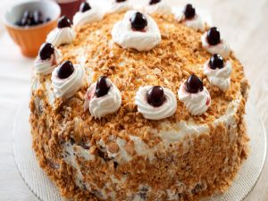 Cake with cream, nuts and cherries