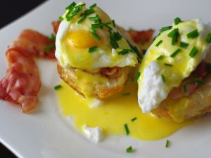 Breakfast of poached eggs with hollandaise sauce and bacon