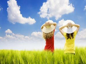 Two girls with hat in a field of green ears