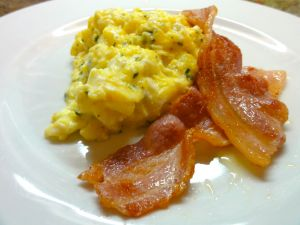Scrambled eggs with herbs, cheese and slices of bacon
