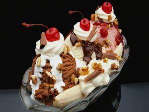 Dish with ice cream, bananas, whipped cream and cherries