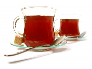 Two cups of tea with brown sugar cubes