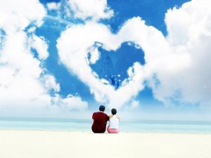 Couple on a beach looking at a heart shaped cloud
