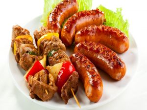 Sausages and meat skewers with onion and tomato