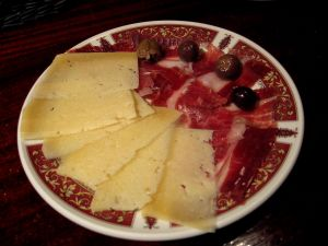 Tapa of Serrano ham and cheese with some olives