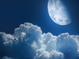 The Moon next to a cottony clouds