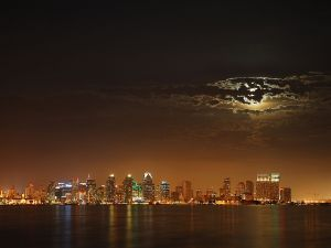The moon hides behind the clouds over the city of San Diego, California