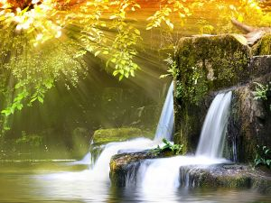 Sun rays illuminating a waterfall