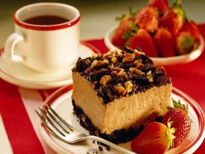 Cake with nuts, strawberries and a cup of coffee