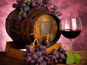 A barrel, a glass of wine and purple grape clusters