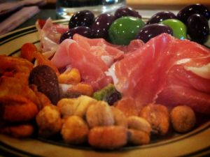 Appetizer with ham, olives and dried fruit