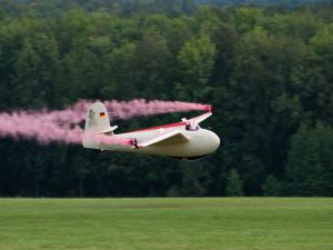 Small plane firing pink smoke