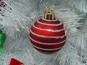 Red ball on a white Christmas tree