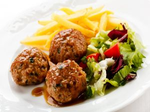 Meatballs in sauce with chips and salad