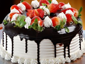 Cream cake decorated with strawberries and chocolate