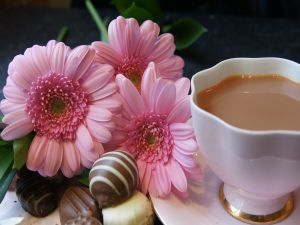Tea with milk, chocolates and flowers