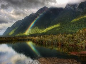 Small rainbow in the mountain and on the water