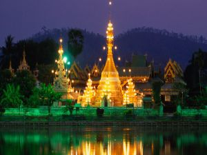 Illuminated building reflected in lake
