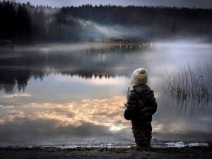 Child looking at a lake at night