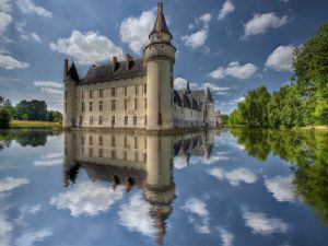 Castle, clouds and trees reflected