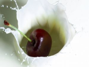 A cherry falling into milk