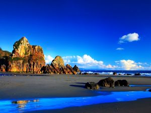 Beach with large rocks and a blue sky