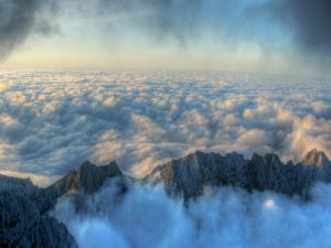 The tops of the mountains peek through the clouds