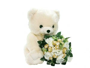A teddy with a bouquet of flowers and chocolates