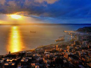 The sun illuminating the sea and buildings