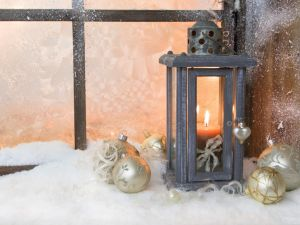 Lantern with candle and white balls in front of a window