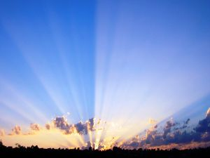 Long rays of the sun in the blue sky