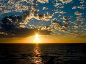 Sky with sun and clouds over the sea at sunset
