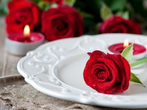 Red rose over a plate and candles