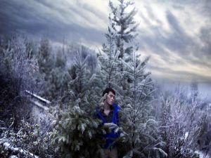 Young man sitting between snowy trees